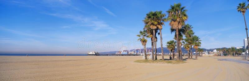 Αυτό είναι η παραλία και η αποβάθρα της Σάντα Μόνικα με το λούνα παρκ της Υπάρχουν φοίνικες στο πρώτο πλάνο στοκ φωτογραφία με δικαίωμα ελεύθερης χρήσης