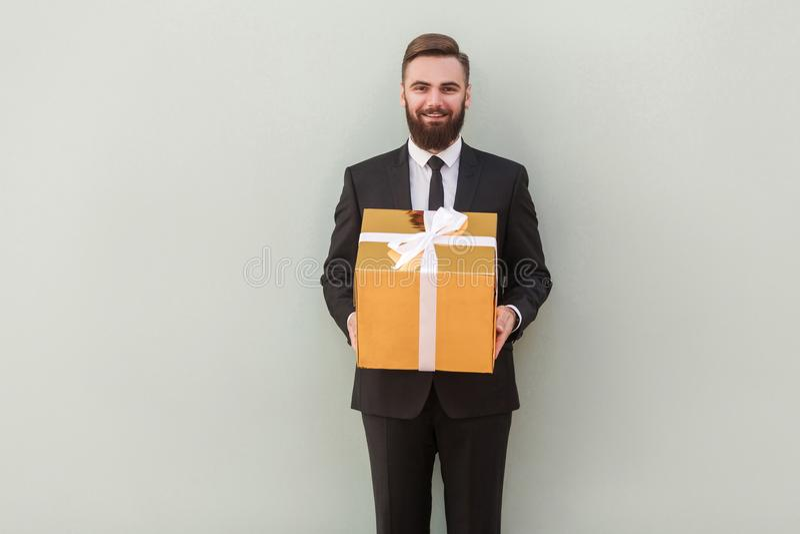 Αυτό κιβώτιο δώρων ` s για σας! Ο τραπεζίτης επιτυχίας δίνει ένα δώρο στοκ φωτογραφία