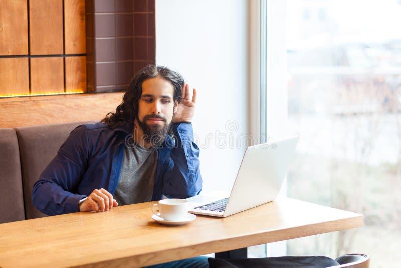 Αυτό που λέτε; Ενδιαφέρον όμορφο νέο ενήλικο άτομο freelancer στην περιστασιακή συνεδρίαση ύφους στον καφέ και την ομιλία με το φ στοκ φωτογραφία με δικαίωμα ελεύθερης χρήσης