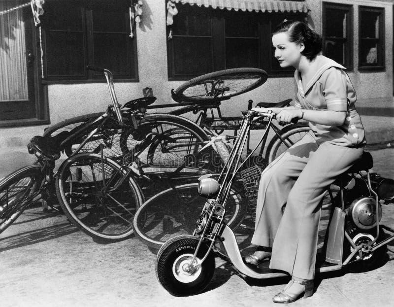 Αφήνοντας τα ποδήλατα στη σκόνη, μια νέα γυναίκα φαντάζεται μια μικροσκοπική μοτοσικλέτα (όλα τα πρόσωπα που απεικονίζονται δεν ζ στοκ εικόνες