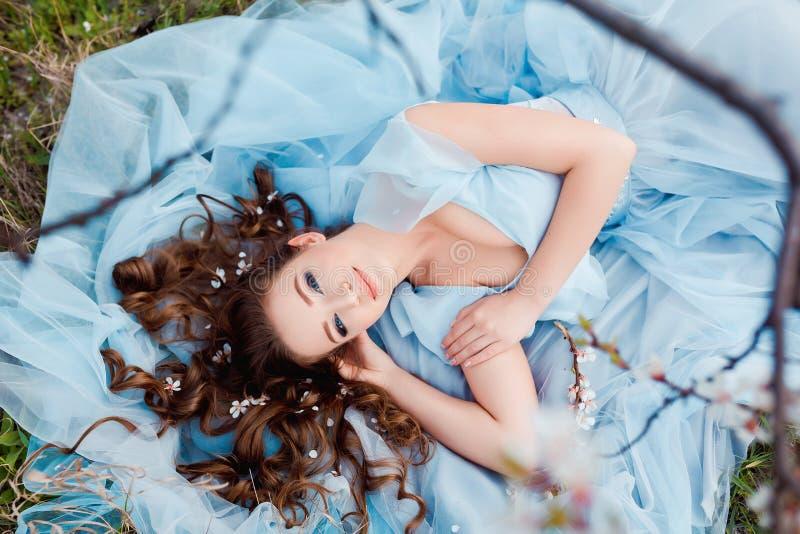 Αφή άνοιξη Η ευτυχής όμορφη νέα χαμογελώντας γυναίκα στο μπλε φόρεμα απολαμβάνει τα φρέσκα λουλούδια και το φως ήλιων στο πάρκο α στοκ εικόνες με δικαίωμα ελεύθερης χρήσης