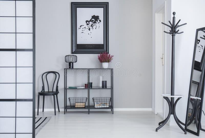 Αφίσα επάνω από τα ράφια με τα λουλούδια και λαμπτήρας στο άσπρο απλό εσωτερικό αιθουσών με το ράφι και τη μαύρη καρέκλα στοκ φωτογραφία με δικαίωμα ελεύθερης χρήσης
