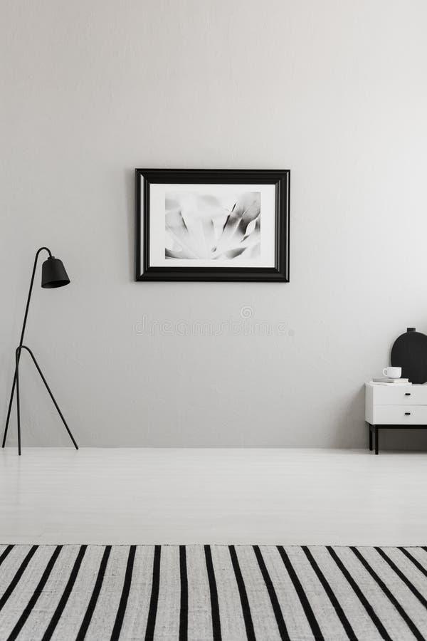 Αφίσα στον γκρίζο τοίχο στο εσωτερικό καθιστικών με το ριγωτό τάπητα στοκ φωτογραφίες με δικαίωμα ελεύθερης χρήσης