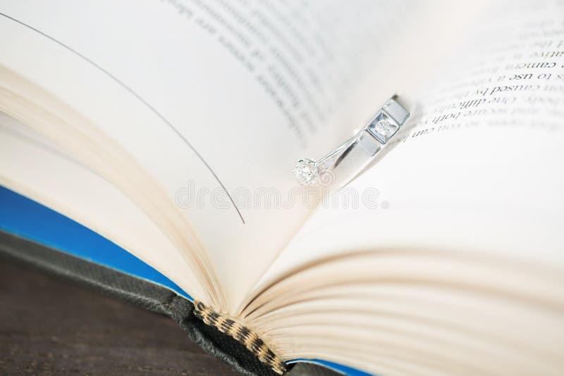 Αφαιρέστε ένα ζευγάρι της δέσμευσης δύο γαμήλιων δαχτυλιδιών σε μια σελίδα βιβλίων στοκ εικόνες