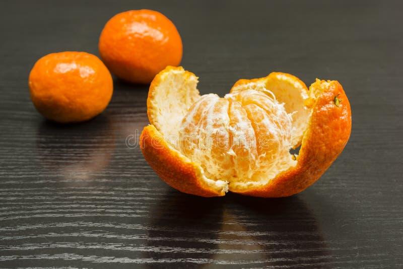 Αφαιρούμενη φλούδα από τα ώριμα φρούτα ενός γλυκού μανταρινιού στοκ φωτογραφίες με δικαίωμα ελεύθερης χρήσης