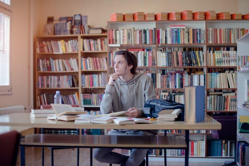 Αφηρημάδα φοιτητών πανεπιστημίου στη βιβλιοθήκη στοκ φωτογραφία με δικαίωμα ελεύθερης χρήσης
