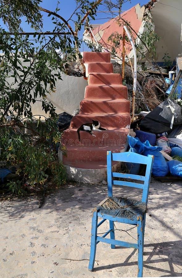 Αφηρημένα κόκκινα σκαλοπάτια από ένα ραγισμένο κτήριο από ένα σπίτι σε Santorini και μια μπλε καρέκλα στοκ εικόνες