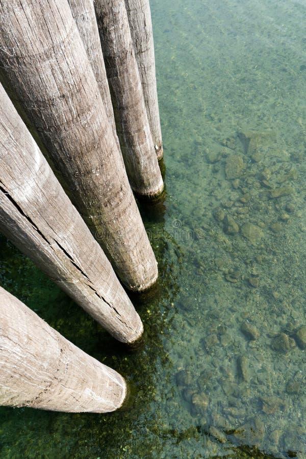 Αφηρημένη άποψη των ψηλών παχιών ξύλινων πυλώνων σε ένα λιμάνι με τα σαφή μπλε ρηχά νερά στοκ φωτογραφία με δικαίωμα ελεύθερης χρήσης