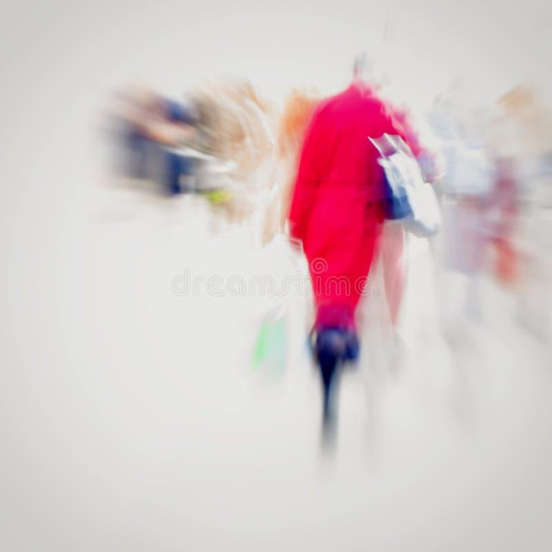 αφηρημένη ανασκόπηση Σκόπιμη θαμπάδα κινήσεων Κορίτσι με την τσάντα στο κόκκινο παλτό που περπατά στο πεζοδρόμιο Έννοια των εποχώ στοκ εικόνα με δικαίωμα ελεύθερης χρήσης