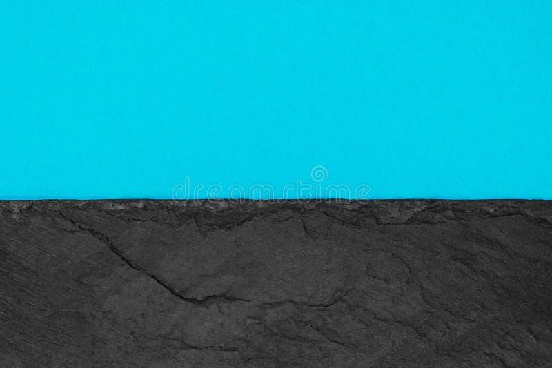 Αφηρημένη σύνθεση υποβάθρου διαιρεσμένος στο μισό ματ ζωηρό μαλακό μπλε έγγραφο χρώματος και τη μαύρη πέτρα με το διάστημα αντιγρ στοκ εικόνες
