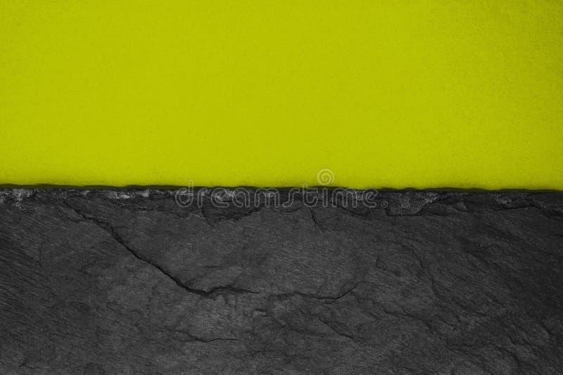 Αφηρημένη σύνθεση υποβάθρου διαιρεσμένος στο μισό ματ σκοτεινό κιτρινωπό πράσινο έγγραφο χρώματος και τη μαύρη πέτρα με το διάστη στοκ εικόνες με δικαίωμα ελεύθερης χρήσης