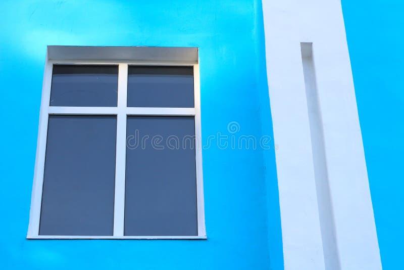 αφηρημένη φωτογραφία ενός παραθύρου με έναν σταυρό χωρισμάτων σε έναν μπλε τοίχο και μια άσπρη ορθογώνια στήλη στοκ φωτογραφίες