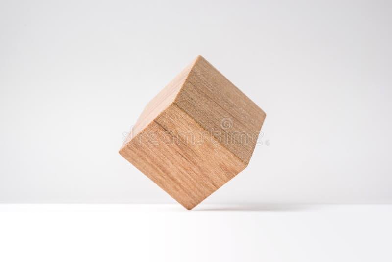 Αφηρημένος γεωμετρικός πραγματικός ξύλινος κύβος με το υπερφυσικό σχεδιάγραμμα στο άσπρο υπόβαθρο στοκ φωτογραφία
