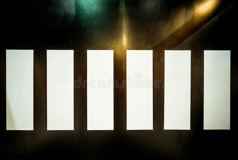 Αφηρημένος τοίχος με τα φω'τα, τις σκιές, και τις σκόνες, διάστημα αντιγράφων σε πέντε κενές κάθετες αφίσες στοκ φωτογραφία