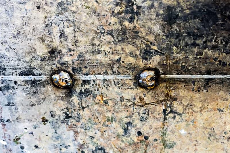 Αφηρημένο βάναυσο υπόβαθρο Ηλικίας επιφάνεια μετάλλων με μια ενωμένη στενά ραφή σε μέση και δύο καρφιά χάλυβα στοκ φωτογραφίες με δικαίωμα ελεύθερης χρήσης