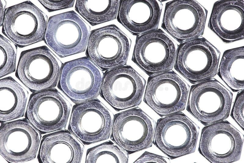 Αφηρημένο μέρος υποβάθρου της κινηματογράφησης σε πρώτο πλάνο καρυδιών μετάλλων που απομονώνεται στο λευκό στοκ εικόνες