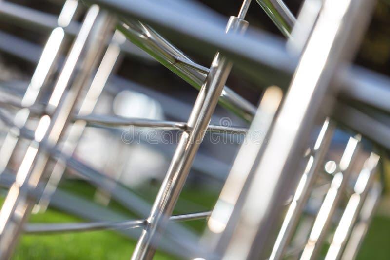 Αφηρημένο μεταλλικό φόντο από χρώμιο, λυγισμένοι σωλήνες διαφορετικών διαμέτρων με φαινόμενο θολώματος στοκ εικόνα