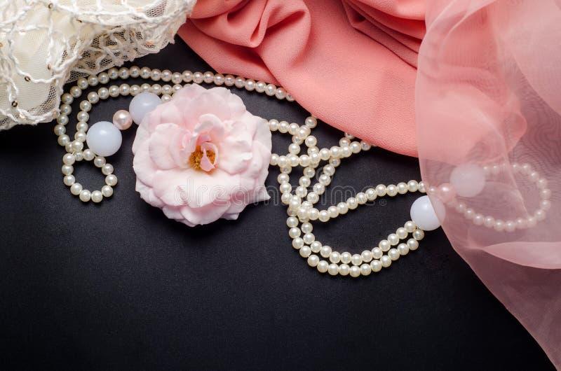 Αφηρημένο υπόβαθρο διακοσμήσεων ομορφιάς με το λουλούδι, το περιδέραιο μαργαριταριών και το ρόδινο ύφασμα στο μαύρο πίνακα στοκ φωτογραφία