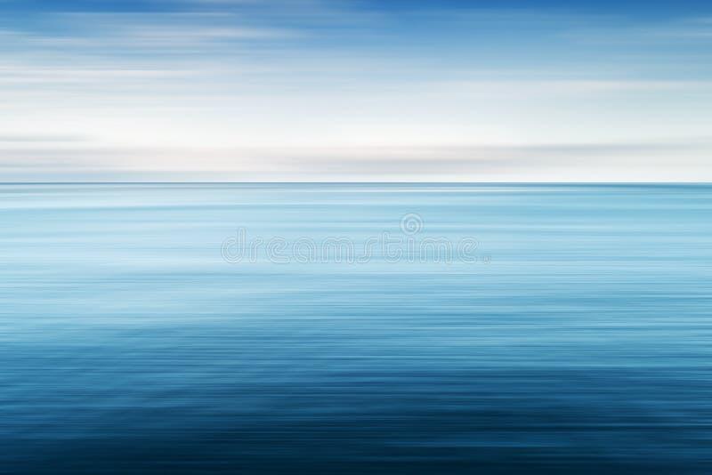 Αφηρημένο υπόβαθρο της μπλε θάλασσας και του νεφελώδους ουρανού πέρα από το Θαλάσσιο νερό και ουρανός θαμπάδων κινήσεων με τα άσπ στοκ εικόνες με δικαίωμα ελεύθερης χρήσης