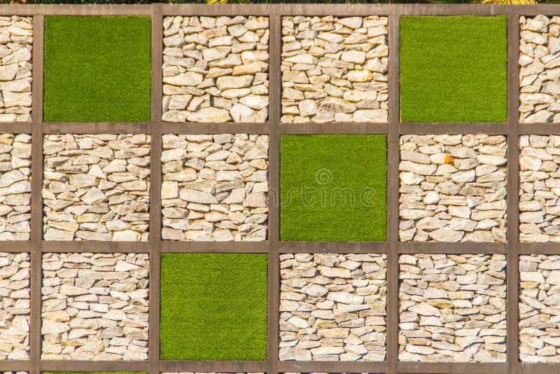Αφηρημένο υπόβαθρο τοίχων πετρών χαλικιών ποταμών με το πράσινο πλαίσιο χλόης Υπόβαθρο τοίχων αμμοχάλικου και πράσινη τετραγωνική στοκ εικόνες