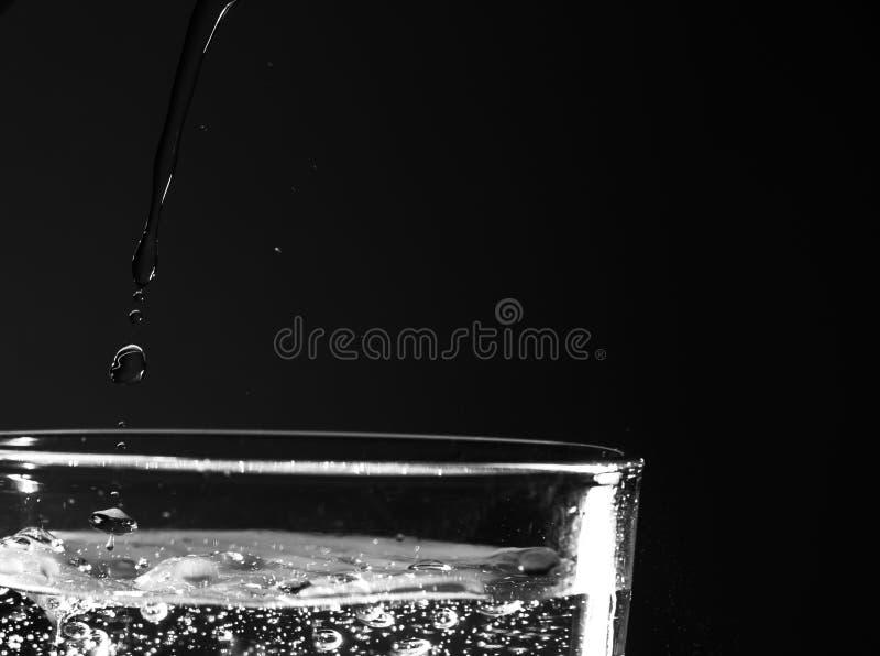 Αφηρημένο υπόβαθρο του έκχυσης του νερού στο γυαλί Πτώσεις νερού Η αιχμή του γυαλιού που γεμίζουν με το νερό και τα σπινθηρίσματα στοκ φωτογραφίες με δικαίωμα ελεύθερης χρήσης