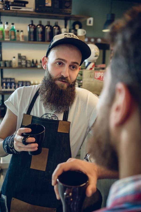 Αφιερωμένος καφές κατανάλωσης hairstylist με τον πελάτη και το φίλο του στοκ εικόνες