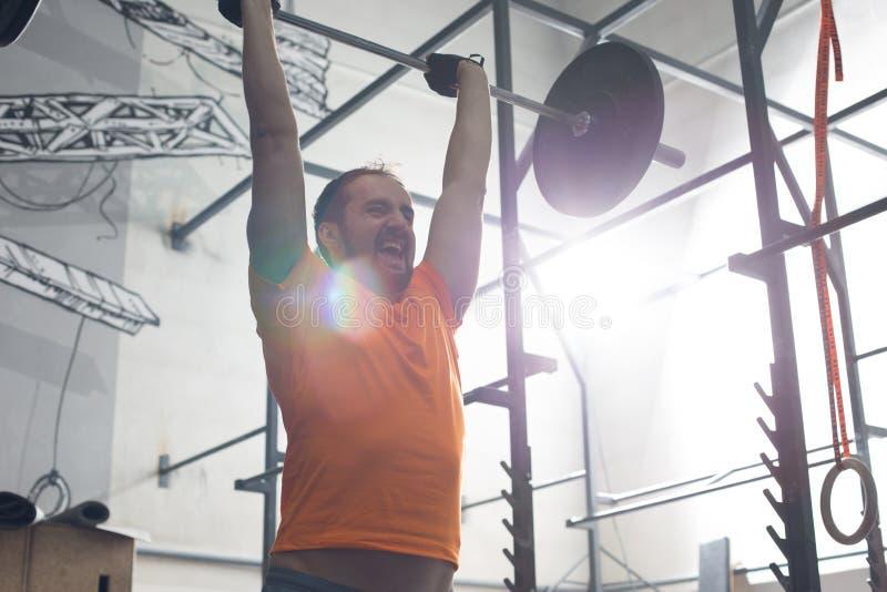 Αφιερωμένο άτομο που ανυψώνει barbell στη γυμναστική crossfit στοκ εικόνα με δικαίωμα ελεύθερης χρήσης