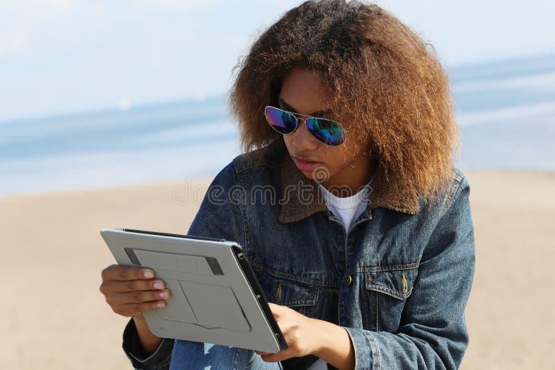 Αφρικανή Αμερικανίδα νέα με ταμπλέτα στην παραλία στοκ φωτογραφίες με δικαίωμα ελεύθερης χρήσης