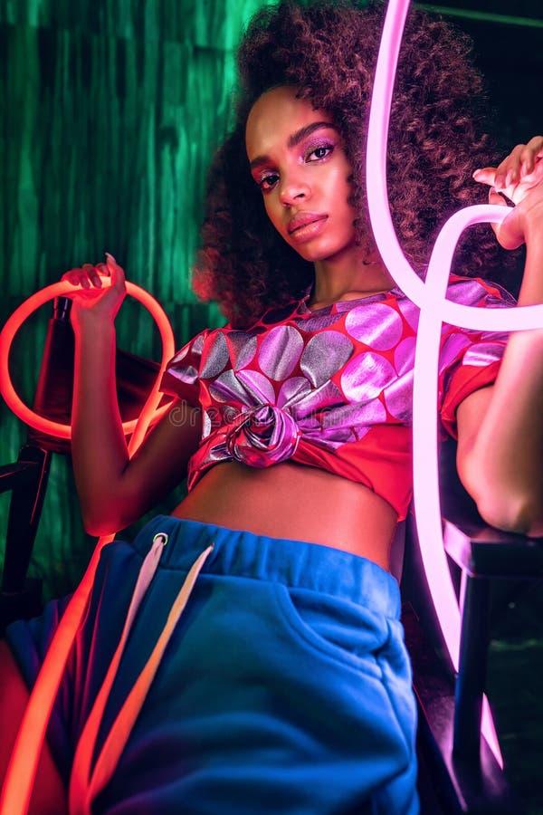 Αφρικανή με ροζ και κόκκινο φως νέον γύρω από τα χέρια στοκ εικόνες με δικαίωμα ελεύθερης χρήσης