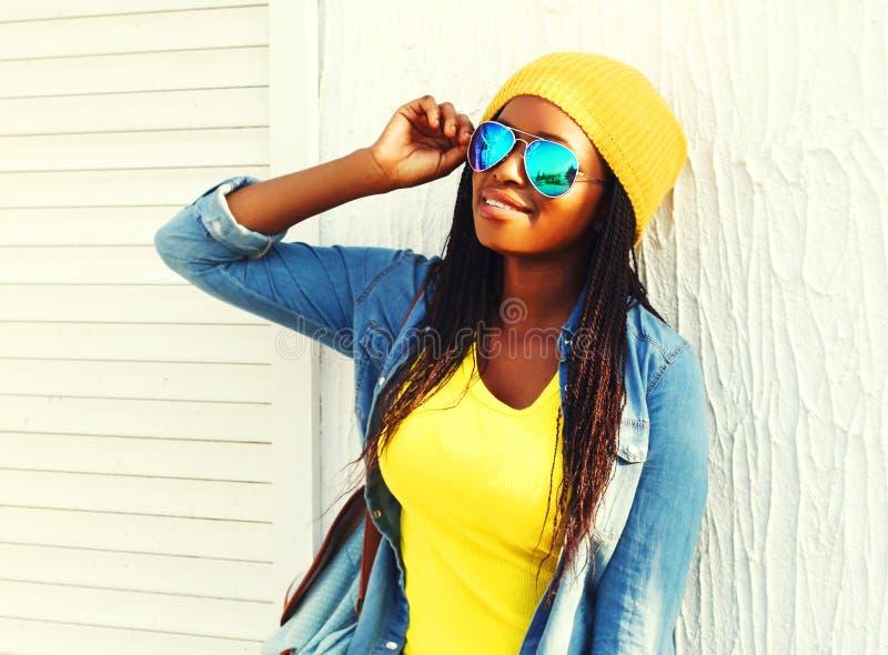 Αφρικανική γυναίκα με skateboard στα ζωηρόχρωμα ενδύματα και τα γυαλιά ηλίου στοκ φωτογραφία με δικαίωμα ελεύθερης χρήσης
