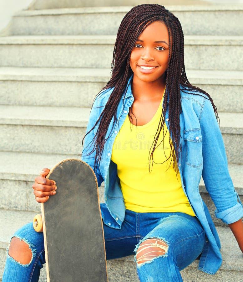 Αφρικανική γυναίκα με skateboard τη συνεδρίαση στην πόλη στοκ εικόνες με δικαίωμα ελεύθερης χρήσης