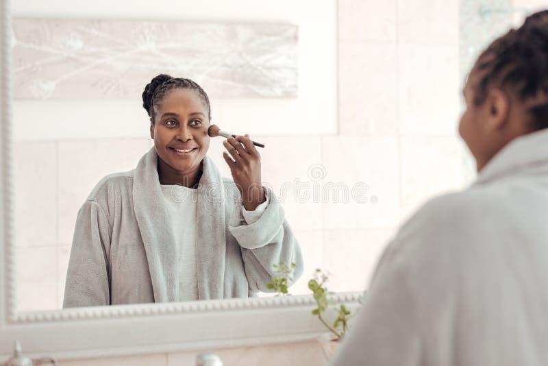 Αφρικανική γυναίκα που εφαρμόζει το ίδρυμα στο μάγουλό της στο λουτρό στοκ εικόνες