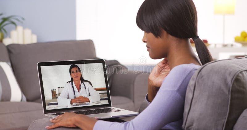 Αφρικανική γυναίκα που μιλά με το γιατρό σε απευθείας σύνδεση στοκ φωτογραφία