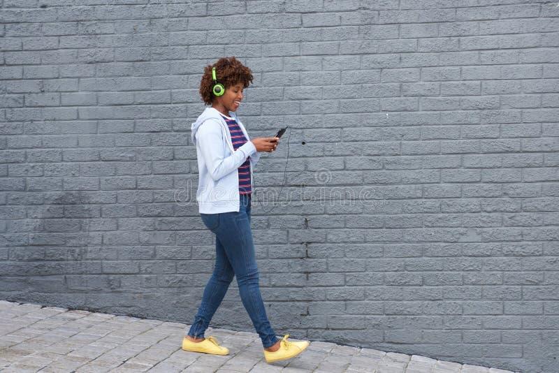Αφρικανική γυναίκα που περπατά και που ακούει τη μουσική στο κινητό τηλέφωνο στοκ φωτογραφία με δικαίωμα ελεύθερης χρήσης