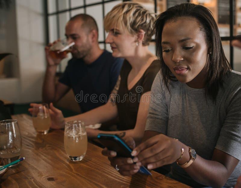 Αφρικανική γυναίκα που πληρώνει το λογαριασμό φραγμών της με μια μηχανή καρτών στοκ φωτογραφία με δικαίωμα ελεύθερης χρήσης