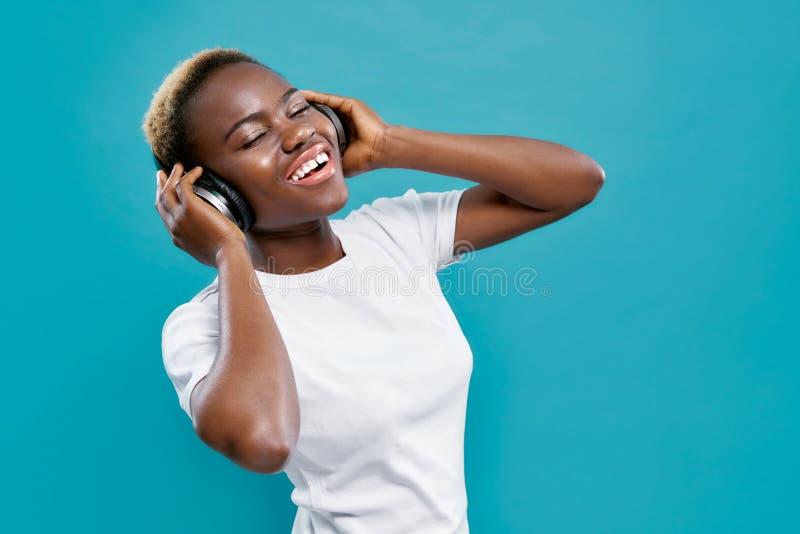 Αφρικανική γυναίκα στα ακουστικά και την απόλαυση bluetooth της μουσικής στοκ εικόνα