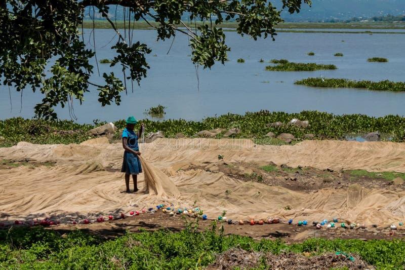 Αφρικανική γυναίκα στην ακτή λιμνών κοντά στη βάρκα που προετοιμάζει το δίχτυ για την αλιεία στοκ εικόνα