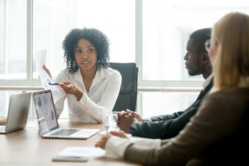 Αφρικανική επιχειρηματίας που παρουσιάζει καλές στατιστικές που πείθουν το multira στοκ εικόνες