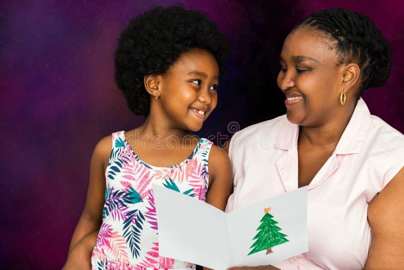 Αφρικανική κάρτα Χριστουγέννων ανάγνωσης μητέρων στο μικρό κορίτσι στοκ εικόνα με δικαίωμα ελεύθερης χρήσης