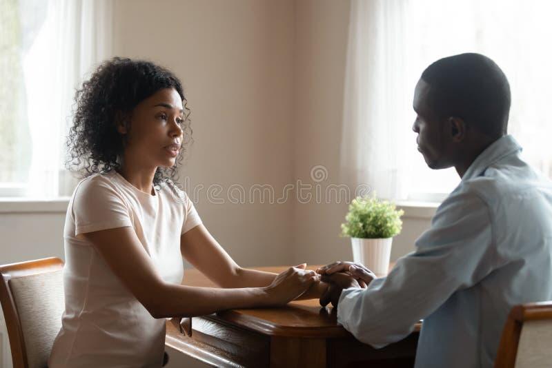 Αφρικανική συνεδρίαση ζευγών στον πίνακα που διοργανώνει τη συζήτηση καρδιά--καρδιών στοκ φωτογραφία με δικαίωμα ελεύθερης χρήσης