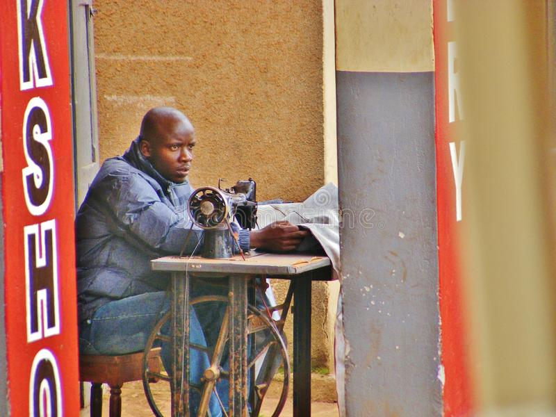 Αφρικανική συνεδρίαση ραφτών στην εφημερίδα ανάγνωσης ράβοντας μηχανών στοκ φωτογραφίες