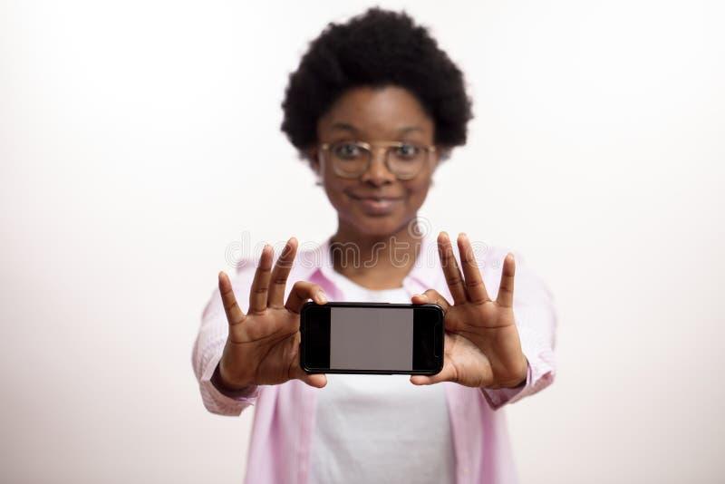 Αφρικανική τρομερή γυναίκα που παρουσιάζει ένα νέο μοντέλο ενός smartphone στοκ φωτογραφία με δικαίωμα ελεύθερης χρήσης