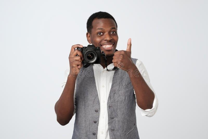 Αφρικανική όμορφη κάμερα και χαμόγελο φωτογραφιών εκμετάλλευσης ατόμων, που παρουσιάζουν αντίχειρα στοκ εικόνες