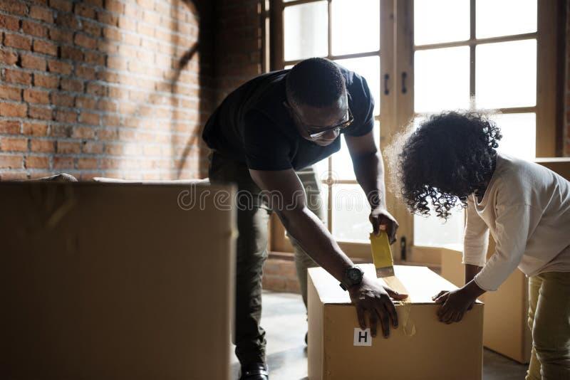 Αφρικανικοί πατέρας και παιδί που ανοίγουν ένα κιβώτιο στοκ φωτογραφία με δικαίωμα ελεύθερης χρήσης