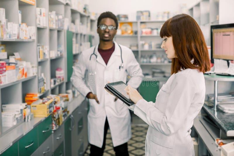 Αφρικανικός άνδρας δύο νέος εύθυμος φαρμακοποιών και καυκάσια γυναίκα που εργάζονται από κοινού Η γυναίκα χρησιμοποιεί την ταμπλέ στοκ φωτογραφία