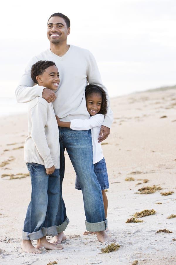 Αφρικανικός-αμερικανικός πατέρας και δύο παιδιά στην παραλία στοκ φωτογραφία