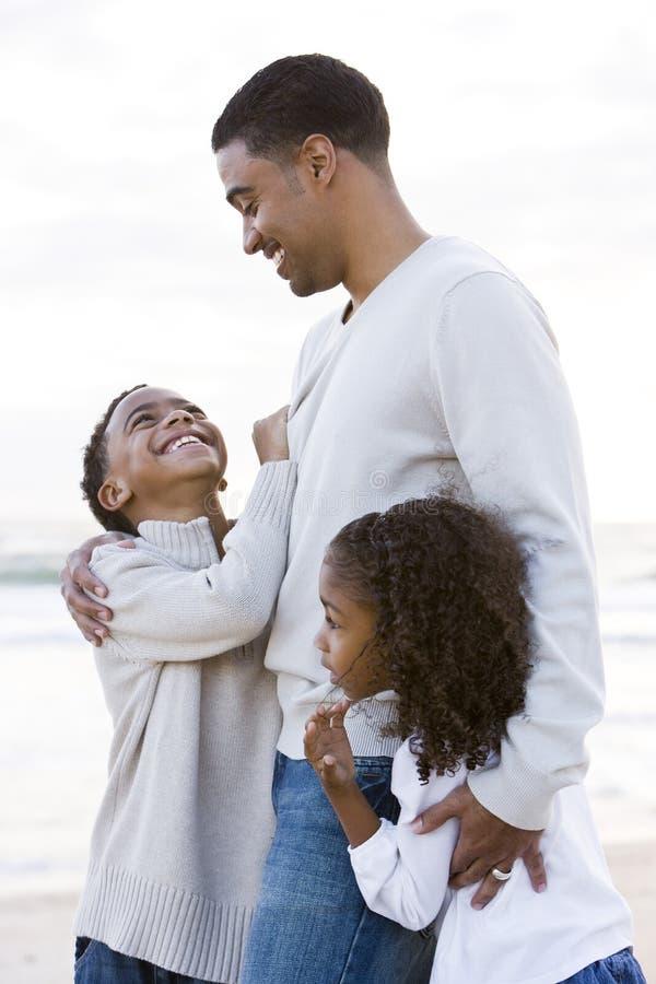 Αφρικανικός-αμερικανικός πατέρας και δύο παιδιά στην παραλία στοκ εικόνα