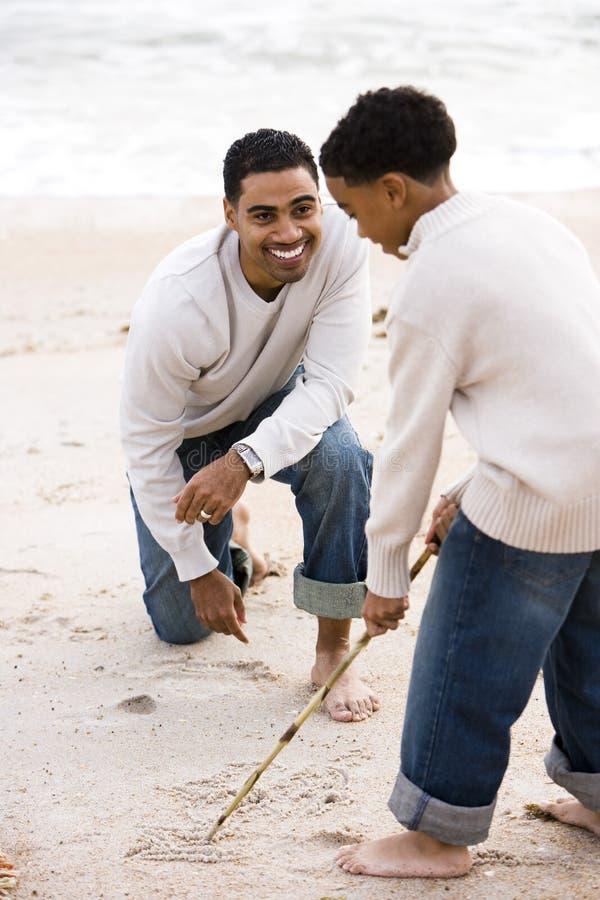 Αφρικανικός-αμερικανικό παιχνίδι πατέρων και γιων στην παραλία στοκ εικόνες με δικαίωμα ελεύθερης χρήσης