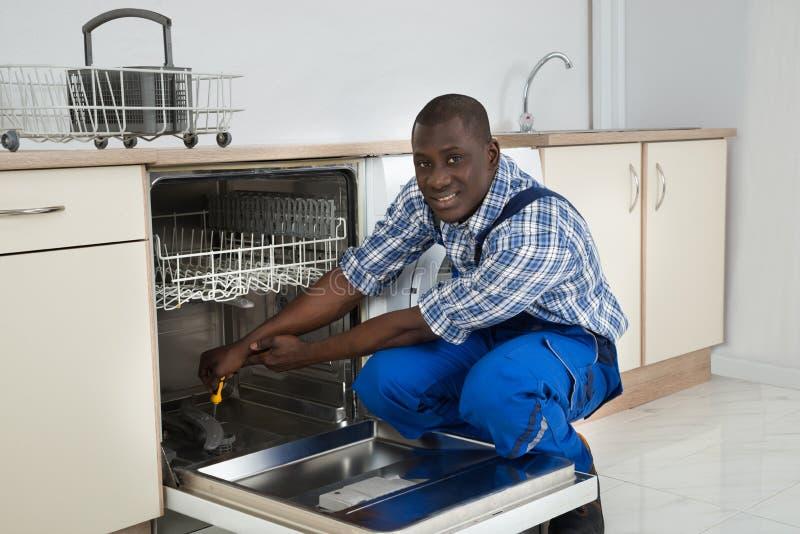 Αφρικανικός επισκευαστής που επισκευάζει το πλυντήριο πιάτων στοκ εικόνα με δικαίωμα ελεύθερης χρήσης