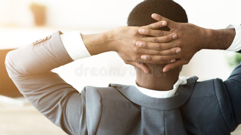 Αφρικανικός επιχειρηματίας που στηρίζεται στο γραφείο, που κάθεται με τα χέρια πίσω από το κεφάλι στοκ φωτογραφίες